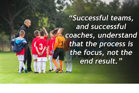 A good youth soccer coach talking to his team