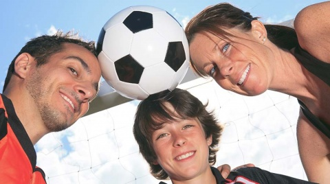 Positive soccer parents and their son holding a soccer ball with their heads